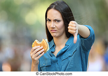 Woman refusing a burger with thumbs down