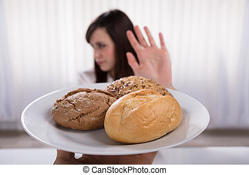 Woman Refusing Plate Of Bread And Cookies