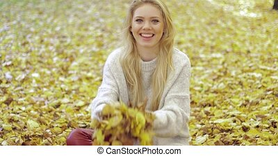 Woman rejoicing at falling leaves - Pretty woman in soft...