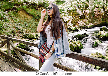 woman relax in autumn forest with waterfall background