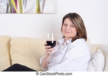 Woman relaxed on sofa with a glass of wine.