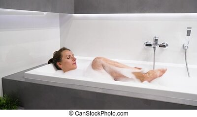 Woman relaxes and takes a bath with foam - Beautiful woman...