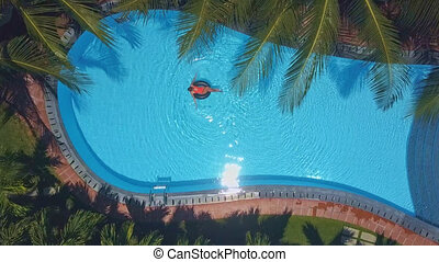 woman relaxes in pool under scorching sun - drone view happy...