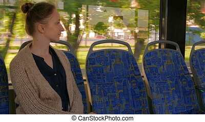 Woman relaxing and looking out of tram window.