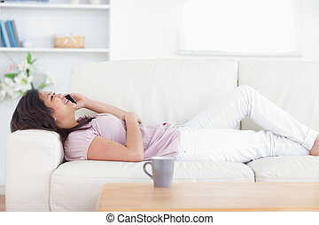 Woman relaxing as she holds a phone in a living room