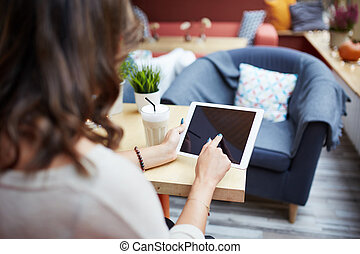 Woman relaxing at cafe using tablet