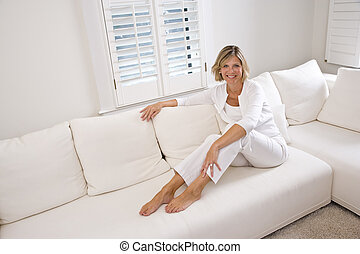 Woman relaxing at home in white living room