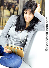 Woman relaxing at home with tablet reading