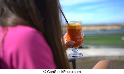 Woman relaxing at outdoor cafe drinking glass of healthy vegetable juice