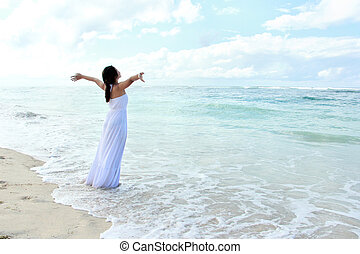 Woman wearing long white dress relaxing at the beach with arms open enjoying her freedom