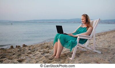 Woman relaxing at the beach with her laptop talking skype -...