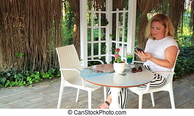 Woman relaxing at the summer cafe