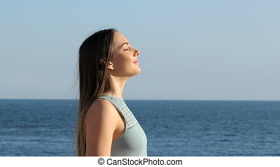 Woman relaxing breathing fresh air on the beach - Side view...