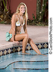 Woman relaxing by swimming pool