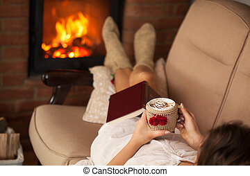Woman relaxing by the fire holding a cup of hot chocolate with cream