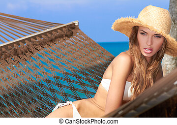 Woman relaxing in a hammock at the beach