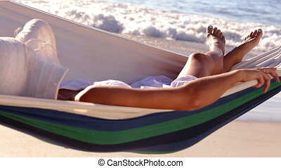 Woman relaxing in a hammock on a sunny beach