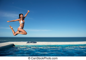 Woman relaxing in a swimming pool - Woman relaxing in the...