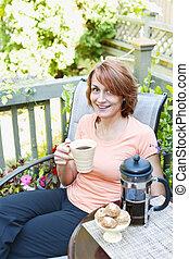 Woman relaxing in backyard