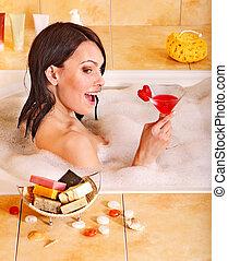 Woman relaxing in bath.