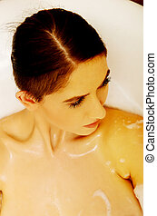 Woman relaxing in bathtub with bubble