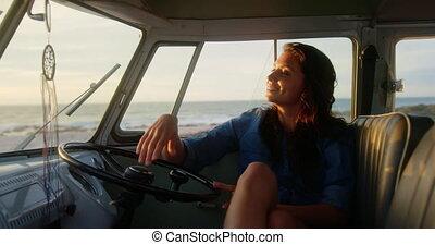 Woman relaxing in camper van at beach 4k - Front view of ...