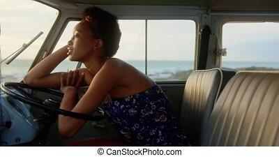 Woman relaxing in camper van at beach 4k