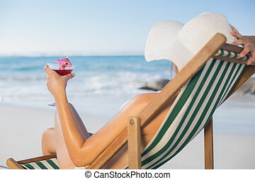 Woman relaxing in deck chair with cocktail