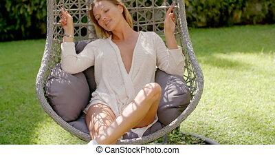 Woman Relaxing in Outdoor Hanging Chair in Garden - Blond...