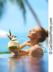 Beautiful blonde woman relaxing in pool holding a tropical fruit cocktail with her head back and eyes closed in bliss