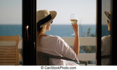 Woman relaxing in solitude. She drinking wine and enjoying sea view