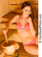Woman relaxing in spa sauna with ladle. Wellbeing - Young...
