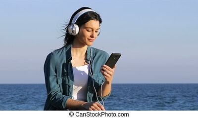 Woman relaxing listening to music on the beach - Happy woman...
