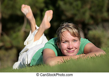 Woman relaxing on a lawn with a nice defocused background