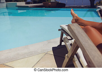 Woman relaxing on a recliner by poolside