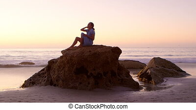 Woman relaxing on a rock in the beach 4k