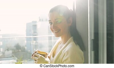 Woman relaxing on balcony holding cup , drinking coffee or tea