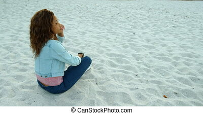 Woman relaxing on beach at dusk 4k - Thoughtful woman...