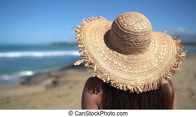 Woman relaxing on beach wearing sun hat fashion summer accessory. View from back of woman enjoying summer holidays.