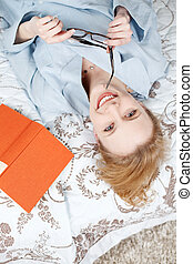 Woman relaxing on bed and reading a book
