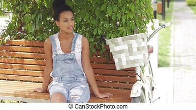 Woman relaxing on bench - Content woman relaxing on wooden...