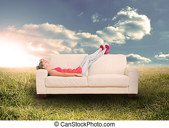 Woman relaxing on couch in field