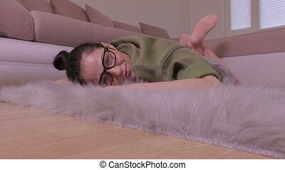 Woman relaxing on grey fur faux rug