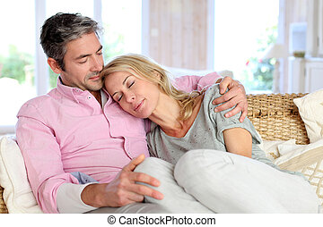 Woman relaxing on husband laid in sofa