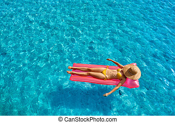 Woman relaxing on inflatable mat float