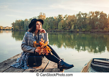 Woman relaxing on lake pier by boat admiring autumn landscape holding branches with leaves. Fall season activities