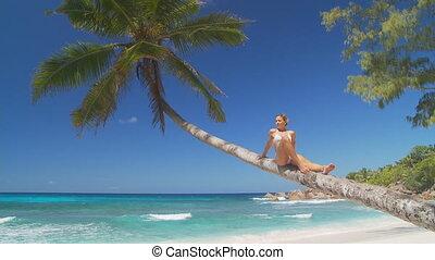 woman relaxing on palmtree