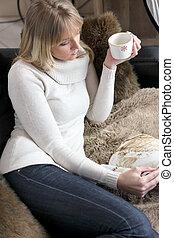 Woman relaxing on sofa with mug of coffee