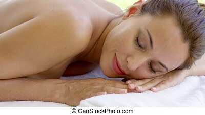 Woman relaxing on spa table on outdoor patio - Adorable...