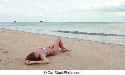 Woman relaxing on the beach near sea